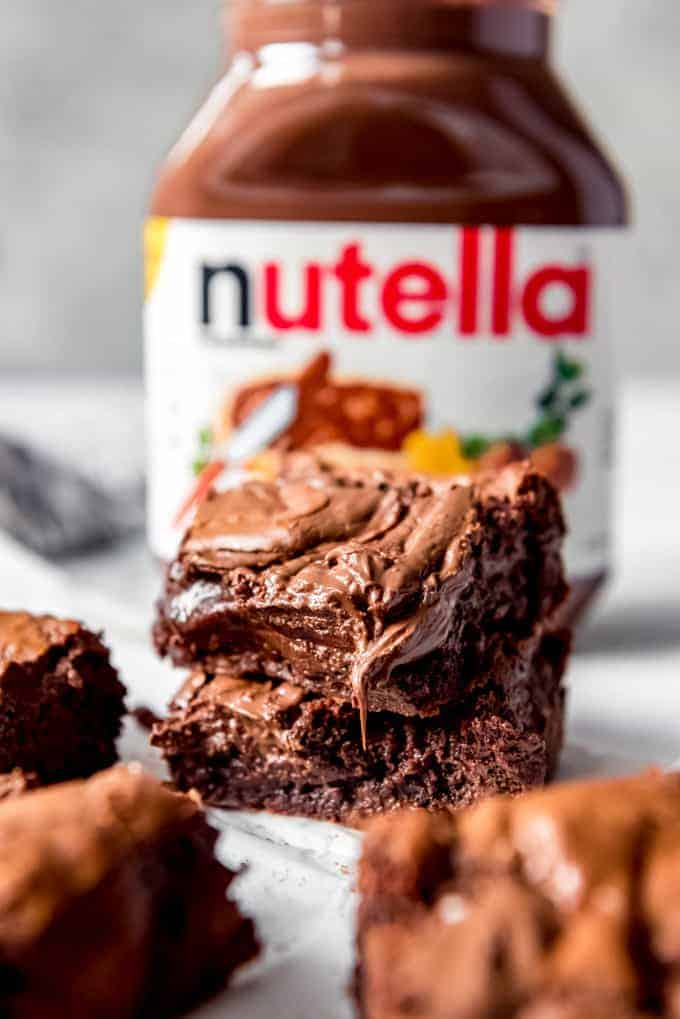 An image of gooey squares of Nutella brownies in front of a jar of Nutella.