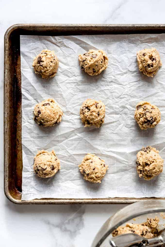 An image of oatmeal cookie dough on a parchment-lined baking sheet.