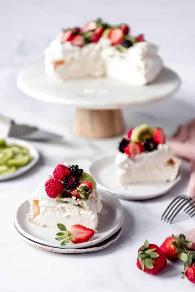 An image of a classic Australian dessert known as pavlova that has been sliced and served on plates with fresh fruit.