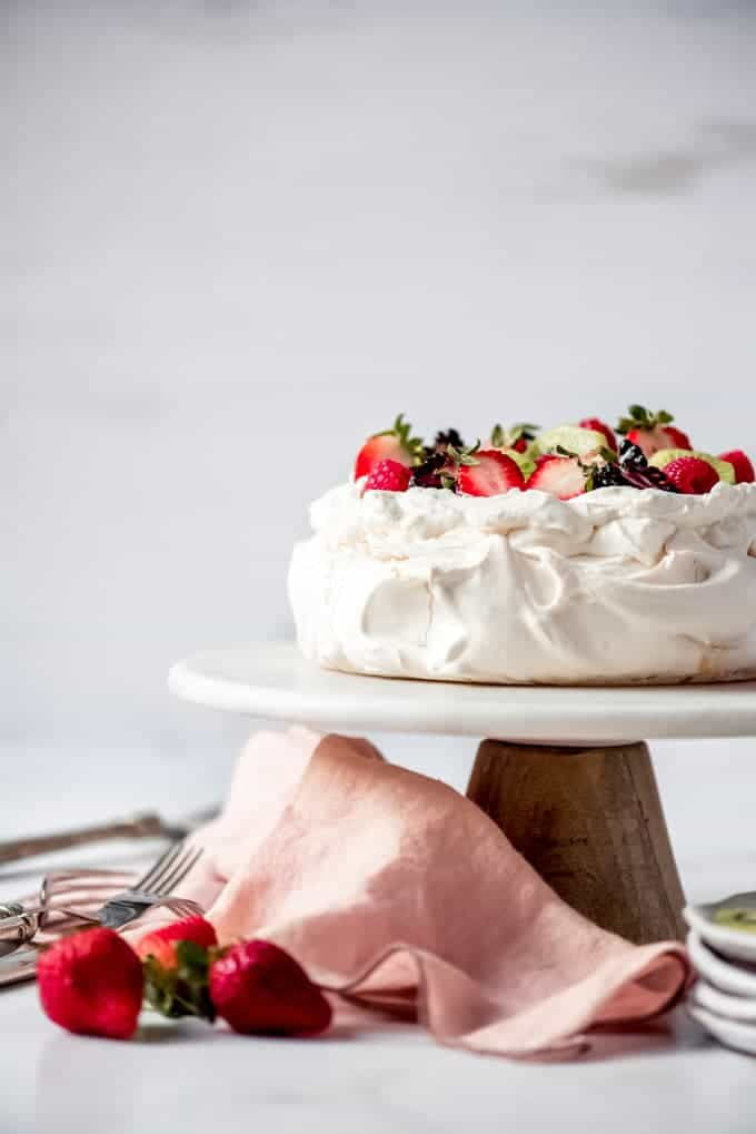 An image of a cake stand with a meringue dessert topped with cream and fresh fruit.