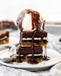 Two slutty brownies stacked on a plate with a scoop of vanilla ice cream on top.