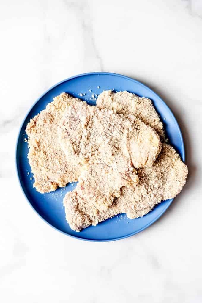 An image of flattened, breaded pork tenderloin on a plate.