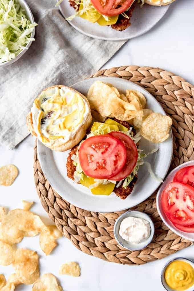 An image of a fried pork sandwich on a plate with chips and toppings like sliced tomatoes.