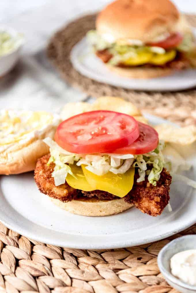 An image of an Indiana pork tenderloin sandwich with lettuce, tomato, and pickles on a bun.