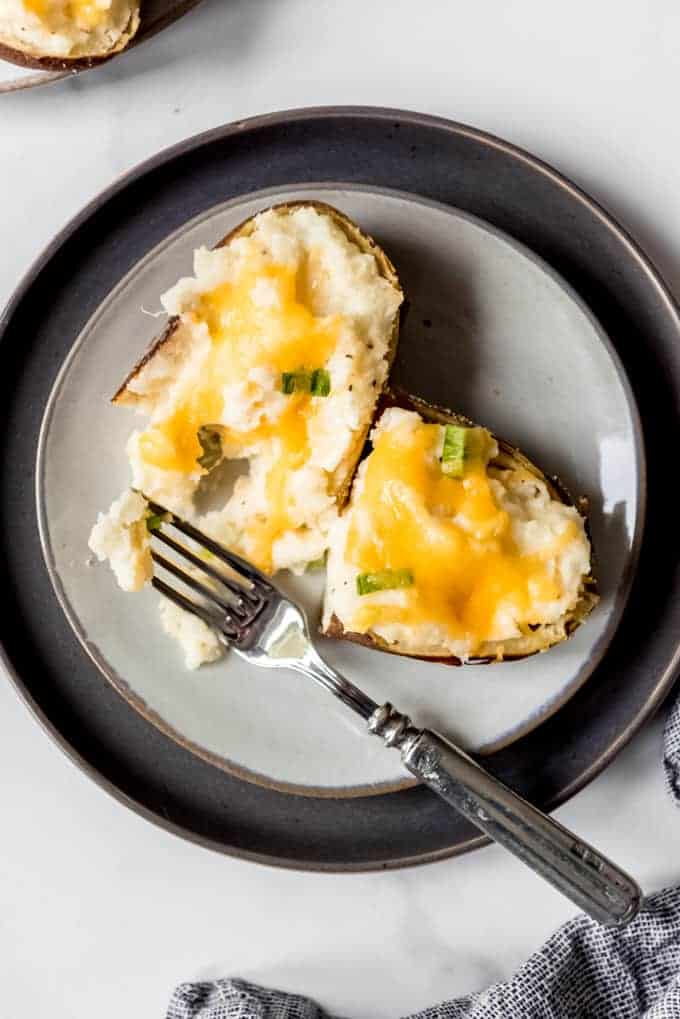 An image of a twice baked potato with cream cheese on a plate.