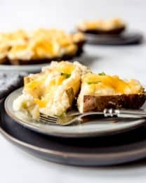 cheesy twice baked potatoes on a plate with a fork, one missing a bite