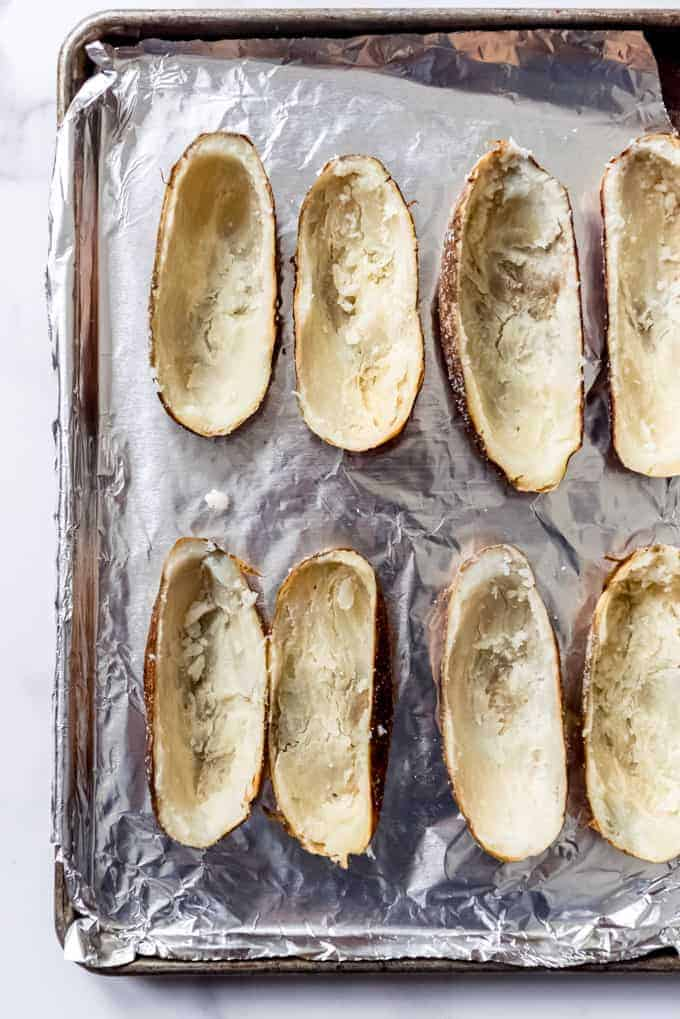 An image of hollowed out potato skins on a foil-lined baking sheet.