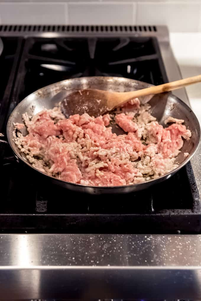 An image of ground chicken being browned in a pan on the stove.