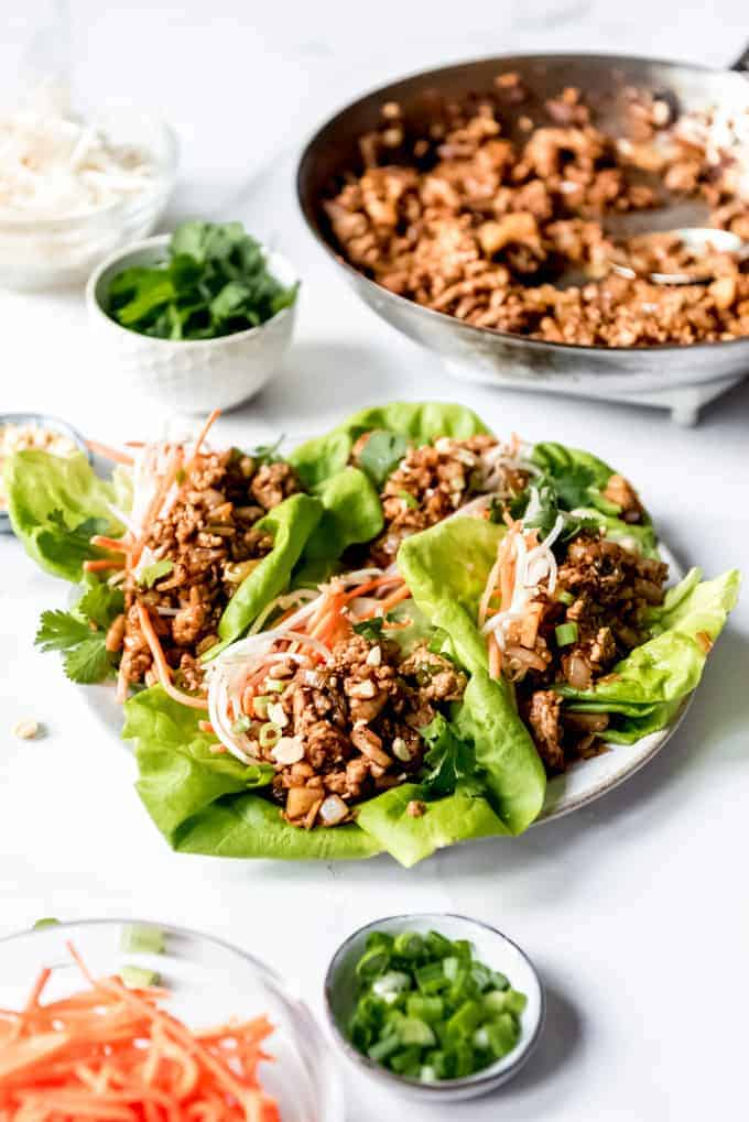 An image of a plate of lettuce wrap appetizers with fixings nearby.