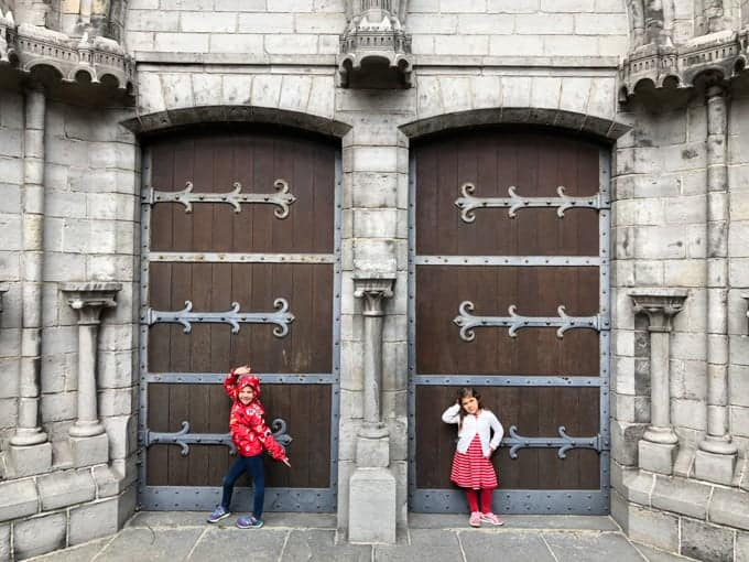 An image of kids in front of gothic doors.