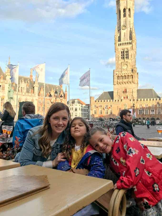 An image of a mother and daughters in the Market Square in Bruges.