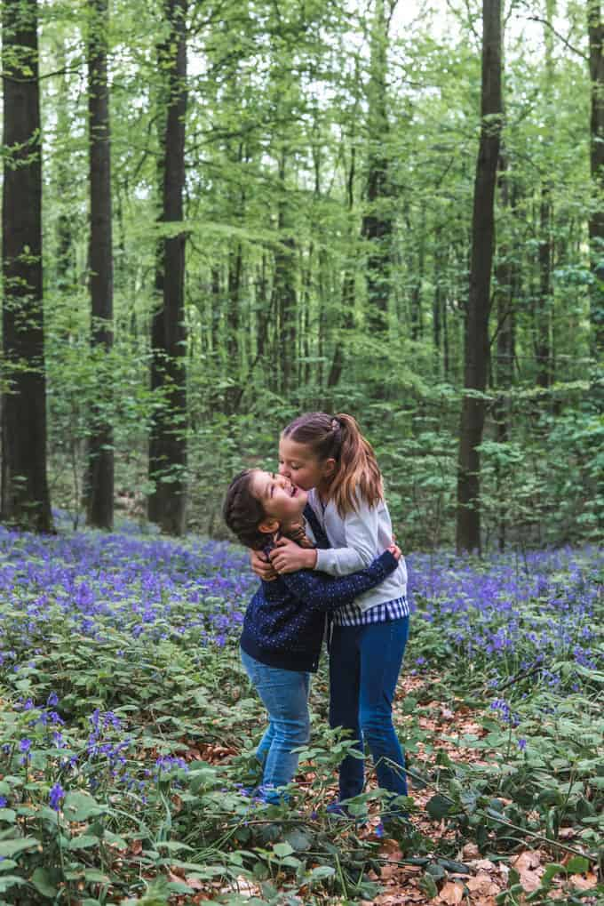 An image of sisters hugging in a forest.