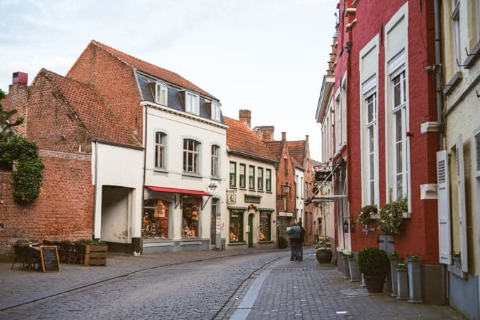 An image of shops along a cobblestone street in a medieval town in Belgium.
