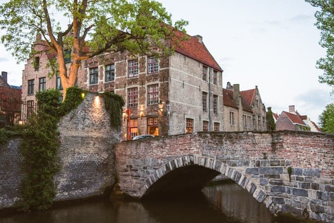 An image of an old bridge over a canal in Europe.