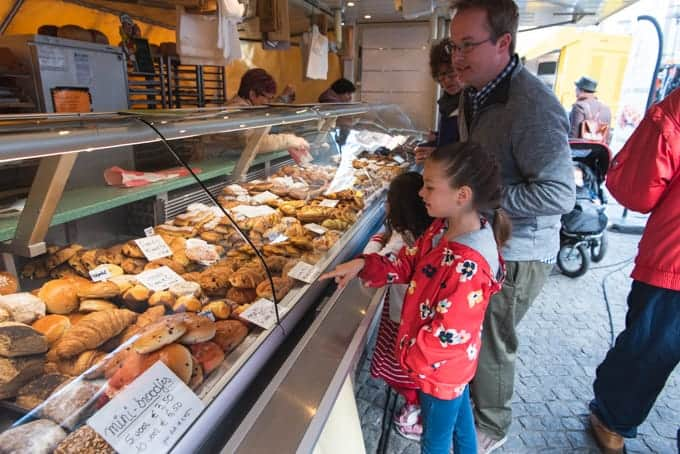 An image of a father and his children picking out pastries from a market in Belgium.