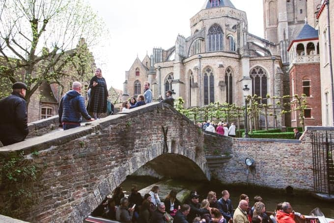 An image of people walking over a bridge in Bruges.