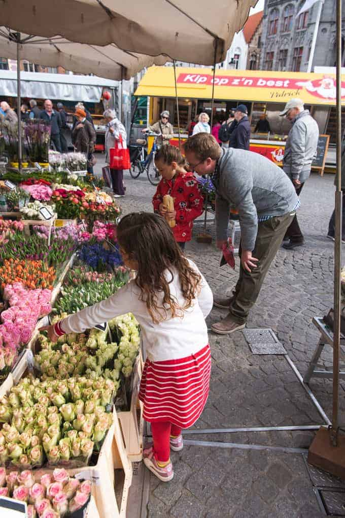 An image of a child picking out flowers at a market in Belgium.