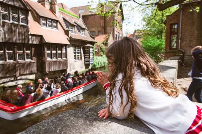 An image of a child waving at a boat of tourists on a canal in Bruges, Belgium.