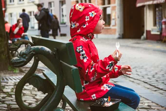 An image of a child in a red jacket eating a waffle on a bench in Bruges.