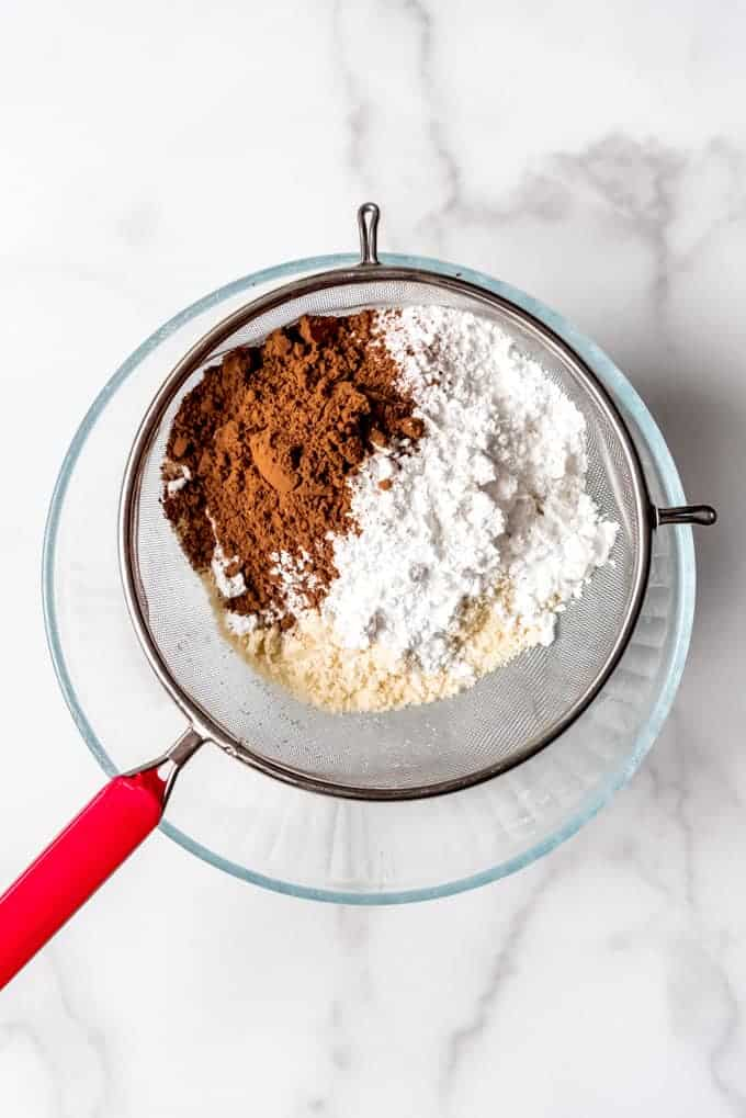 An image of cocoa powder, powdered sugar, and almond meal in a fine mesh sieve for making macarons.