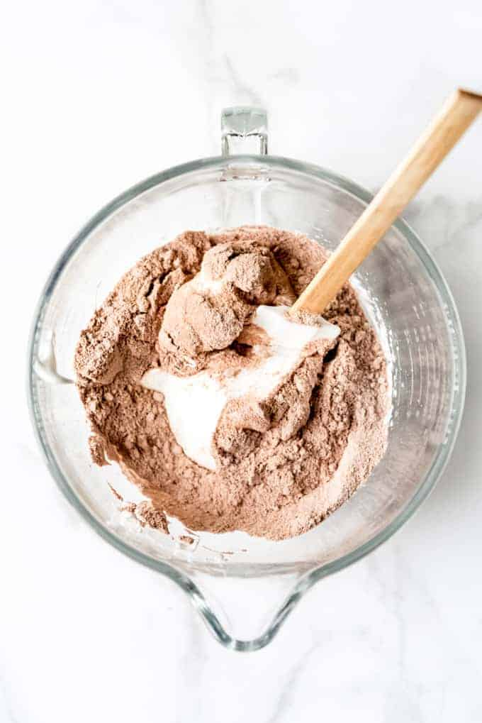 An image showing how to mix sifted almond flour, cocoa powder, and powdered sugar into beaten egg whites.