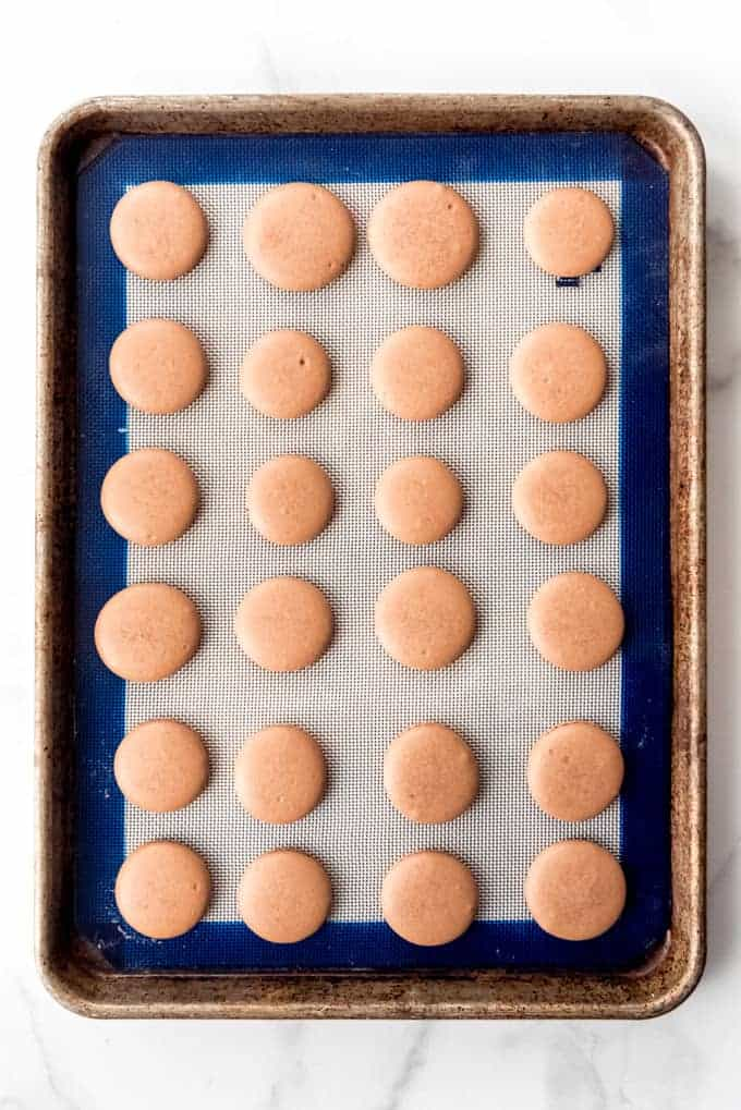 An image of chocolate macaron shells on a silicone baking mat.