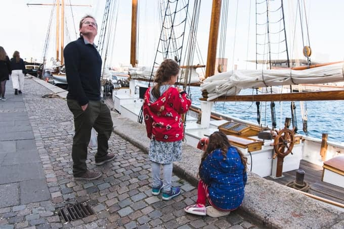 A father and daughters looking at boats.