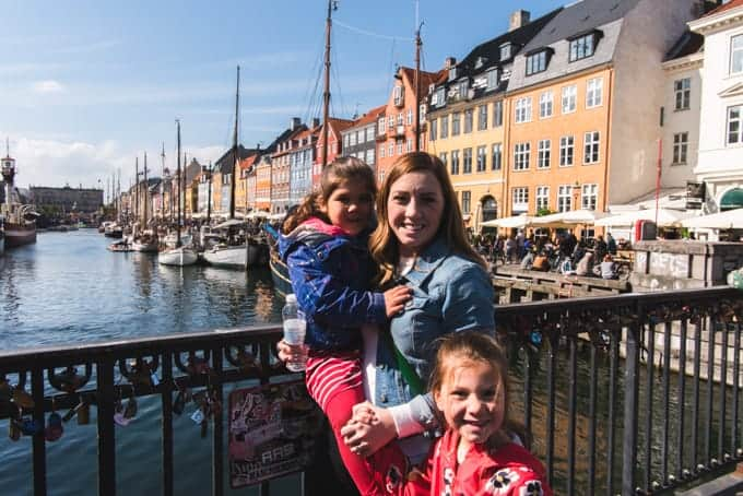 A mom and kids in front of colorful buildings.