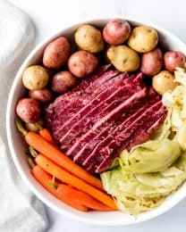 An image of a large plate of sliced corned beef and cabbage with potatoes and carrots.