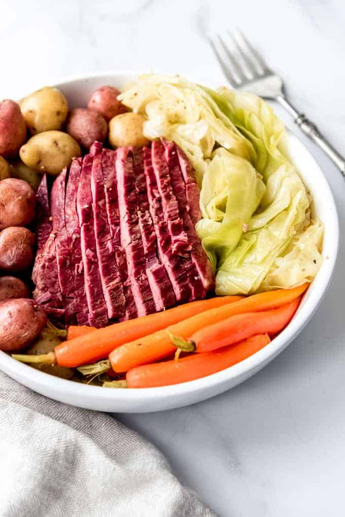 An image of a sliced corned beef brisket served on a platter with boiled potatoes, cooked cabbage, and carrots.