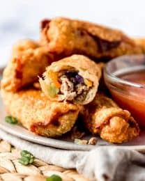 a plate full of crispy eggrolls and a bowl of dipping sauce