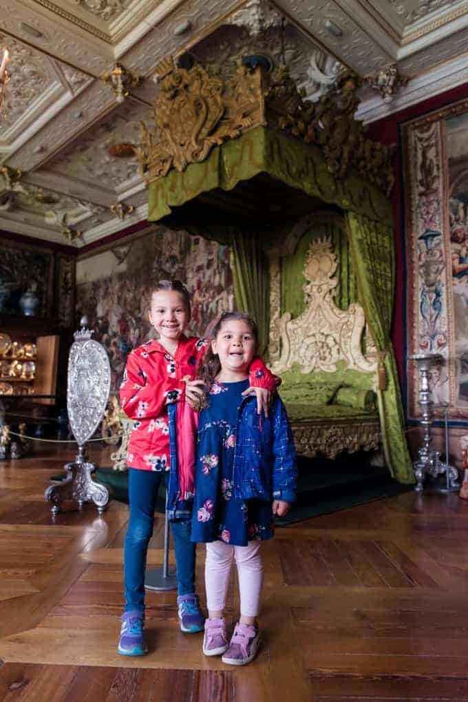 Two girls in a palace bedroom.