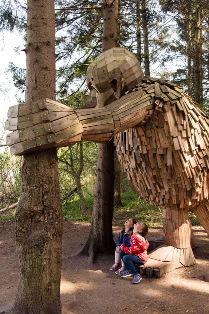 Children looking up at a giant troll in a forest.
