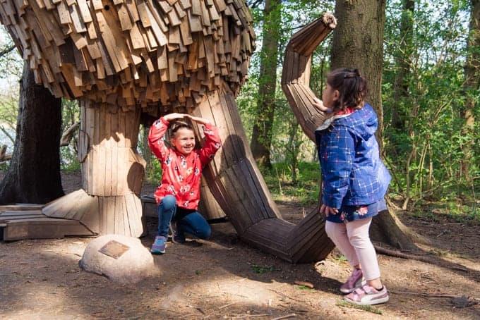 Children playing under a wooden sculpture.