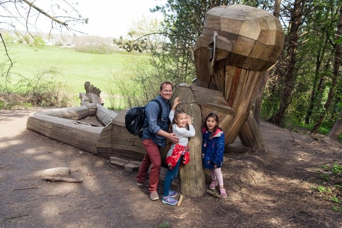 A dad and kids by a wooden giant.