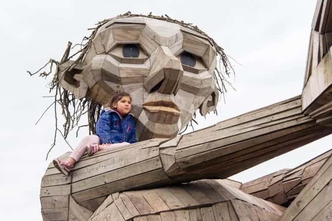 A child sitting on the shoulder of a wooden giant.