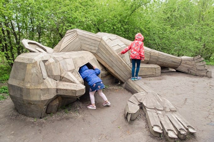 Children playing around a wooden sculpture of a giant.