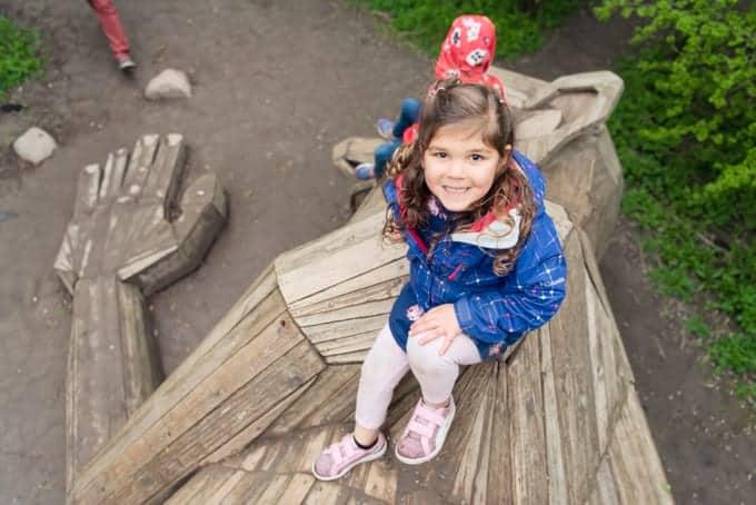 A child on a wooden troll sculpture.