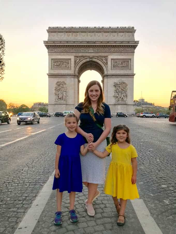 An image of a mother and daughters in front of the Arc de Triomphe.