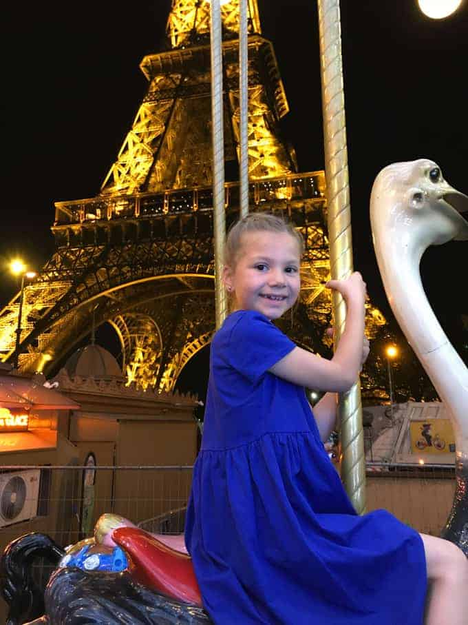 An image of a child riding a carousel in front of the Eiffel Tower at night.