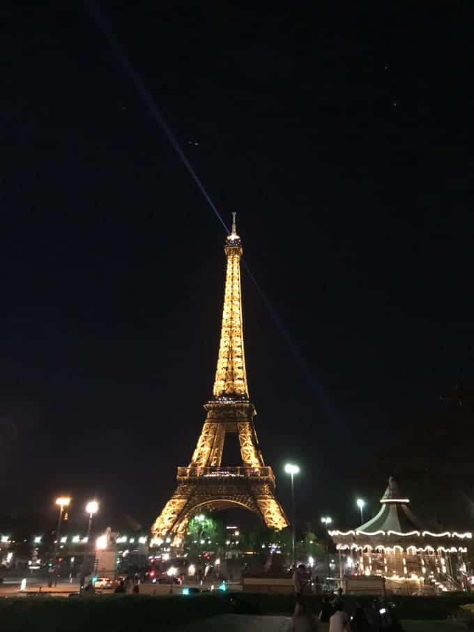 An image of the Eiffel Tower with a carousel in front of it at night.