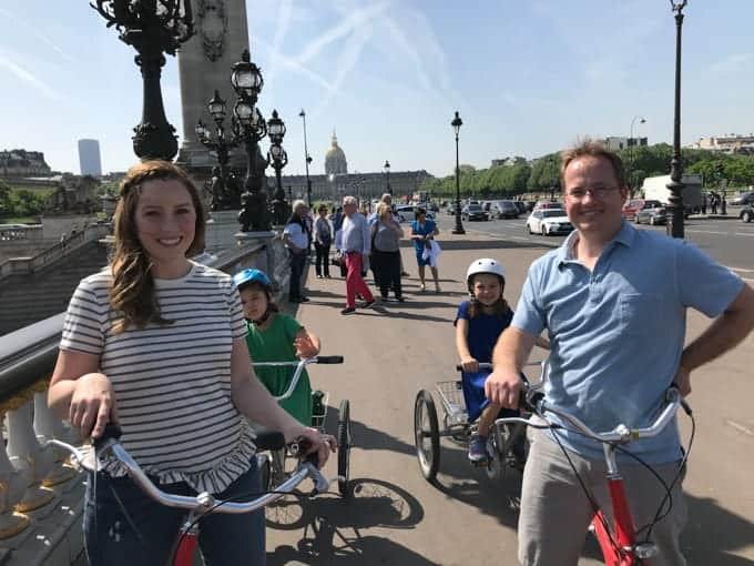 An image of a family riding bikes on a tour through Paris in Spring.