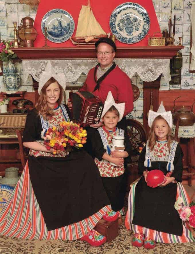 a family of 4 wearing traditional clothing and posing for a family portrait