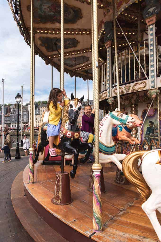 An image of a child riding on a carousel horse in Honfleur, France.