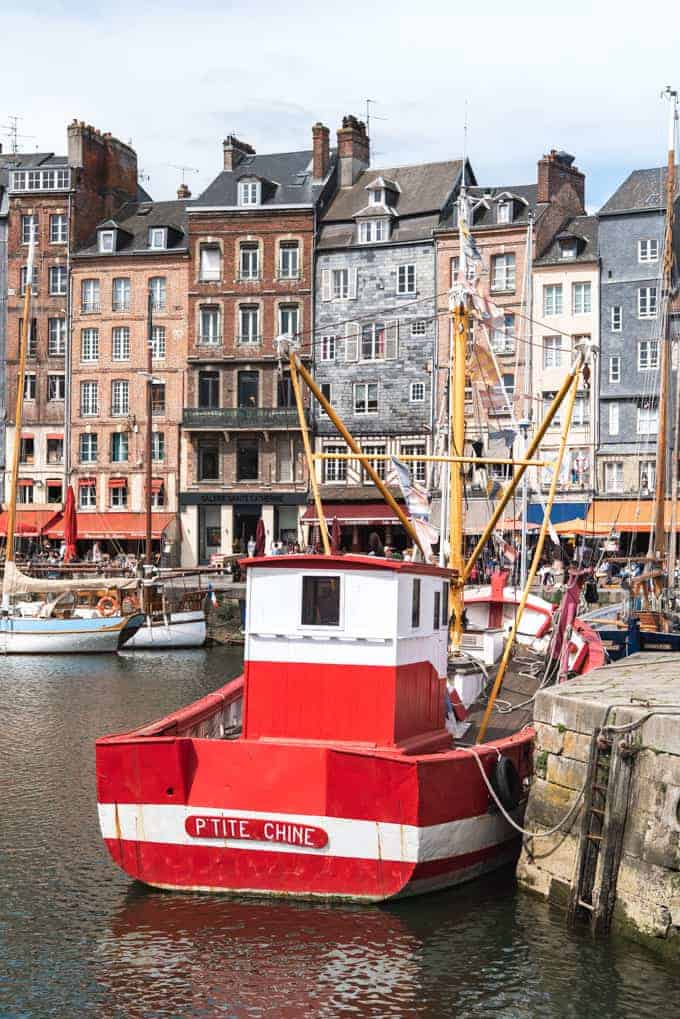 An image of a red boat in the harbor of Honfleur, France.