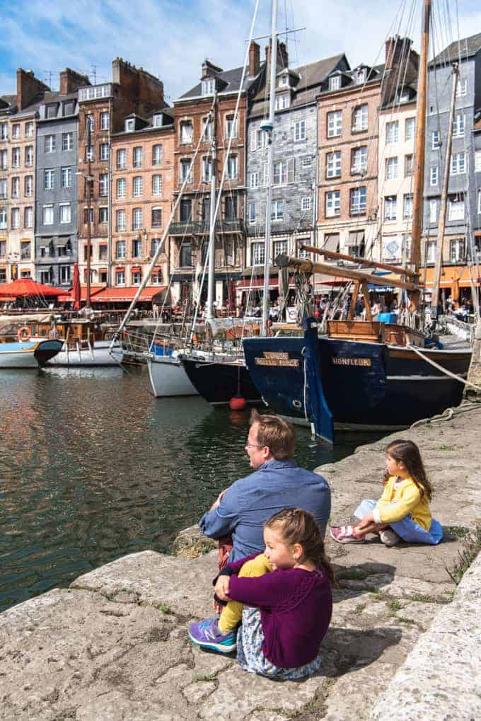An image of a father and children sitting on a stone pier in Honfleur, France.