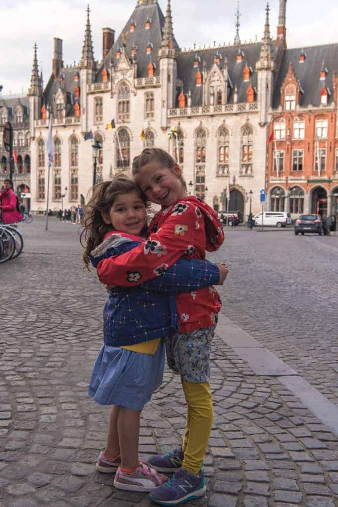An image of two children hugging in the Market Square in Bruges, Belgium.