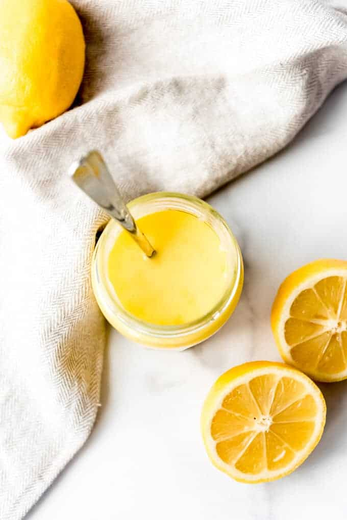 An image of a spoon in a jar of homemade lemon curd.
