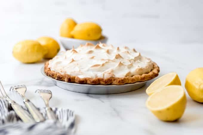 A lemon meringue pie next to a bunch of lemons.