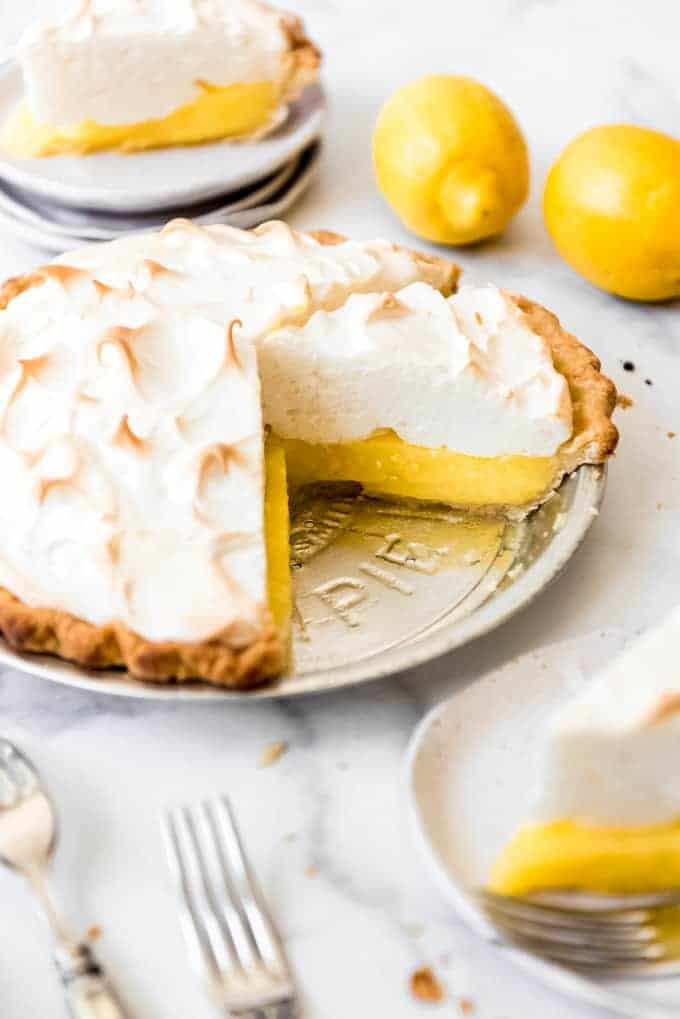 Lemon meringue pie in a metal pie tin with slices on plates next to it.